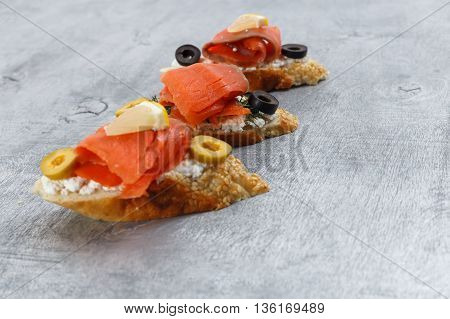 Tasty various italian sandwiches with seafood against rustic wooden background. Crostini with cheese red fish lemon and sliced olives horizontal view with selective focus