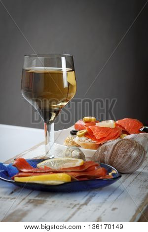 Tasty various italian sandwiches with seafood against rustic wooden background. Crostini with cheese red fish and olives on white plate and wine close up with selective focus