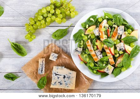 salad with chicken breast spinach celery grapes and cheese Gruyere on a white dish view from above