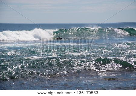 KALBARRI,WA,AUSTRALIA-APRIL 23,2016: Surfer dipping into the wave of the glistening Indian Ocean at Blue Holes Beach in Kalbarri, Western Australia.