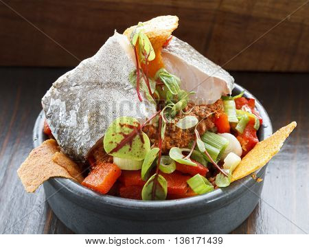 A healthy raw fish salad for lunch served in a grey china bowl.