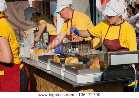 KYIV, UKRAINE - JUN 4, 2016: Femal cooks in uniform of fast-food restaurant cooking fried food during a street fair on June 4, 2016. Kiev is the 8th most populous city in Europe.