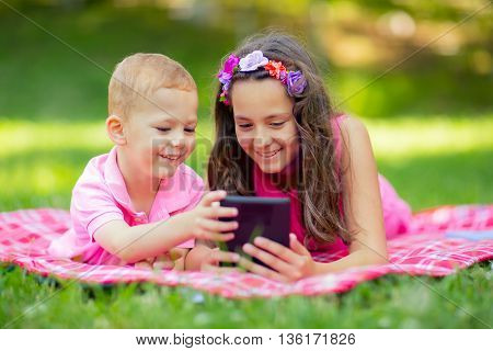 Sister and brother lying down on blanket and using tablet in park