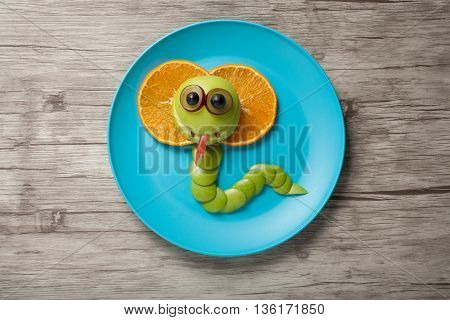 Cobra made of apple and orange on plate and board