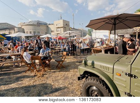 KYIV, UKRAINE - JUN 4, 2016: Big food-court with tables and people eating meals under umbrelas outdoor during city fair on June 4, 2016. Kiev is the 8th most populous city in Europe.