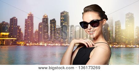 accessories, eyewear, fashion, people and luxury concept - beautiful young woman in elegant black sunglasses over night dubai city lights background