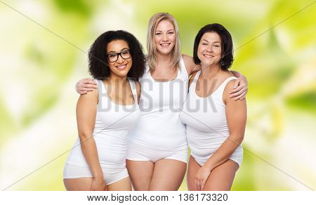 friendship, beauty, body positive and people concept - group of happy plus size women in white underwear over green natural background