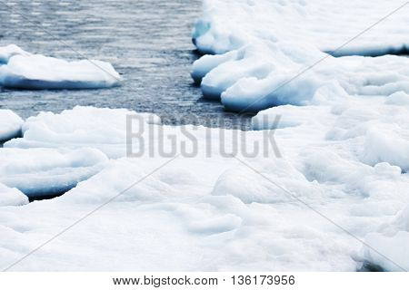 Natural sea ice blocks breaking up against shore and ice during freezing winter weather.