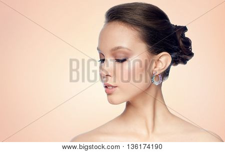 beauty, jewelry, accessories, people and luxury concept - close up of beautiful asian woman face with earring over beige background