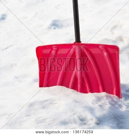 Red plastic shovel for snow removal. Closeup.