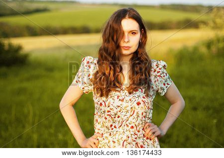 Young Woman Stay Is Burned Field. Woman Stands Facing The Camera