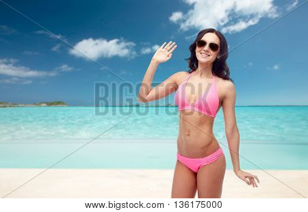 people, travel, tourism, swimwear and summer holidays concept - happy young woman in sunglasses and pink swimsuit waving hand over exotic tropical beach background