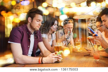 people, leisure, addiction, technology and communication concept - group of friends with smartphones and drinks at bar or pub