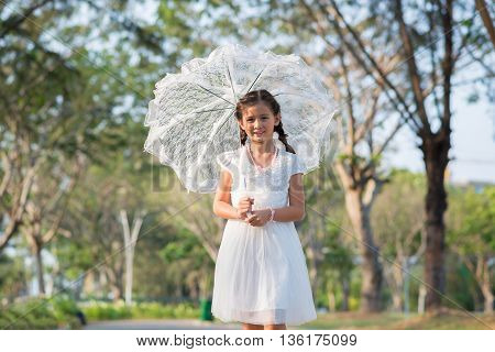 Cute young woman with lace umbrella standing in park