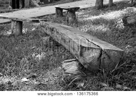 Old Wooden bench made of tree trunks in garden