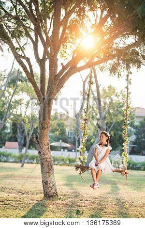 Pretty preteen girl swinging in backyard on sunny day