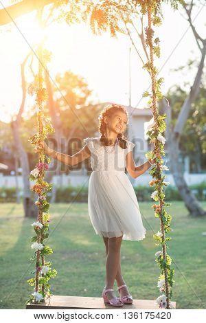 Lovely preteen girl standing on swing outdoors