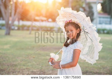 Portrait of preteen girl posing with umbrella outdoors