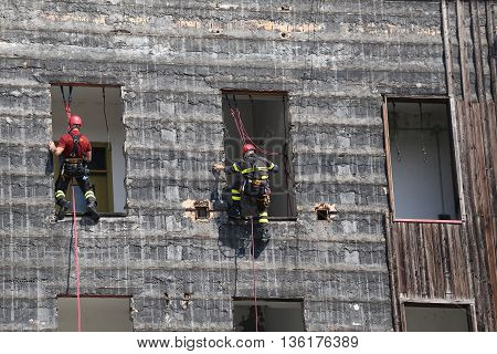 Firefighters Climbing A Wall Of A House During The Fire Drill
