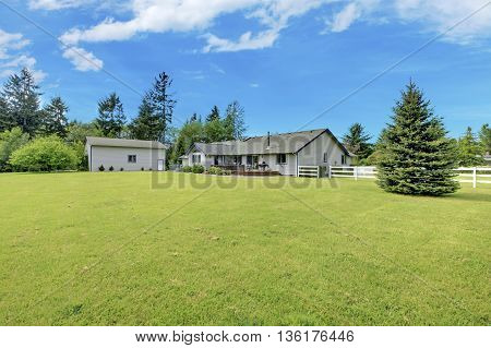 Spacious Backyard Garden With Green Lawn And Shed.