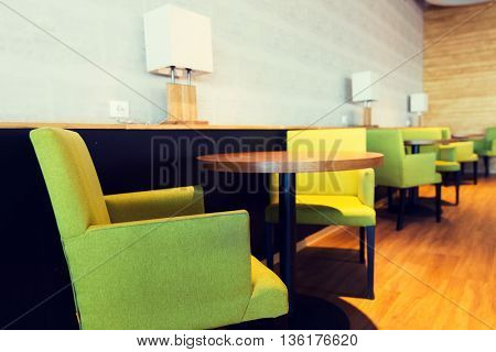 design, public place, furniture and interior concept - close up of restaurant interior with tables and chairs