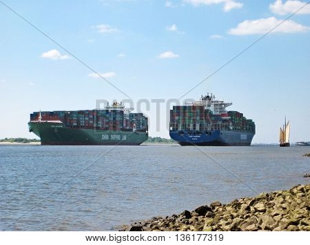 Hamburg Germany - May 24 2008: Big container ships crossing on river Elbe view from riverside.