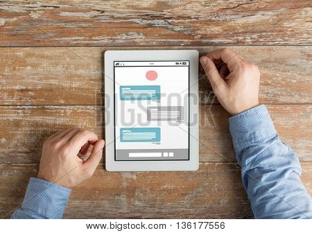 people, internet, online communication and technology concept - close up of male hands with messenger chat on tablet pc computer screen on wooden table