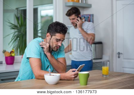 Tensed Man using phone at table with friend on background