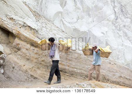 IJEN VOLCANO, INDONESIA - DECEMBER 8 : Unidentified workers carry sulphur inside Ijen crater on December 8, 2011 in Ijen Volcano, Indonesia.
