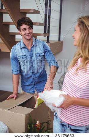 Smiling woman looking at man unpacking books at home
