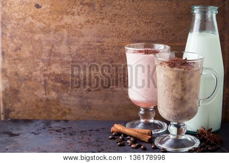 Pink and brown smoothies of chocolate, bananas, milk and raspberry, coffee ice-cream cocktail on dark metal table with rusty background, copy space