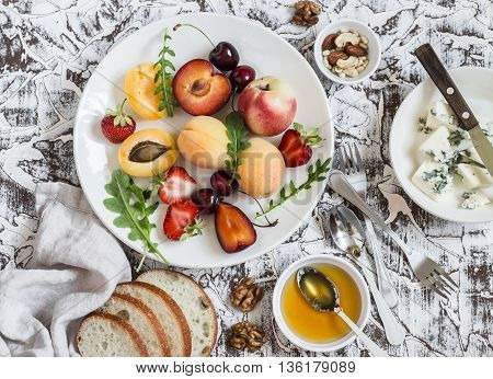 Summer fruits - apricots peaches plums cherries strawberries and blue cheese honey walnuts on a light stone background. Healthy diet vegetarian food. Delicious summer dessert or snack