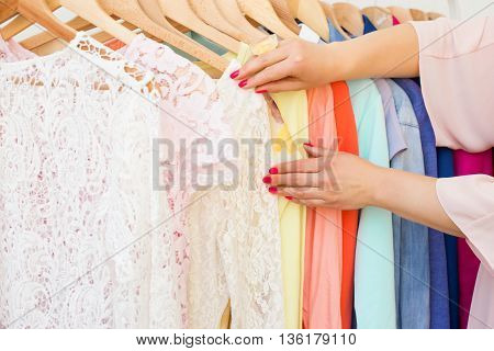 Woman looking at the clothing rack with many different clothes