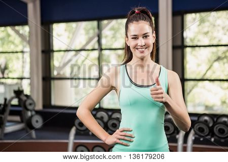 Happy woman showing her thumbs up at gym
