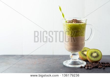 Double layer smoothie of chocolate and kiwi, coffee ice-cream cocktail with straw on dark metal rusty table with white background, copy space at left