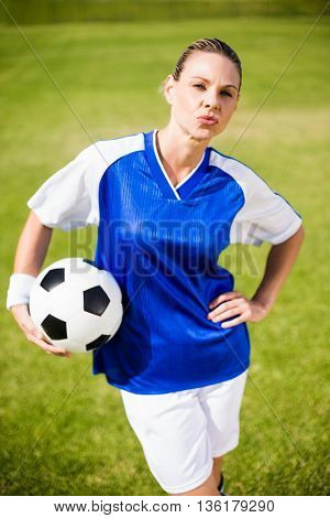 Female football player standing with a ball