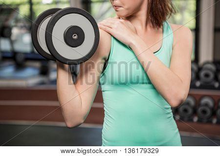 Woman lifting dumbbell at gym