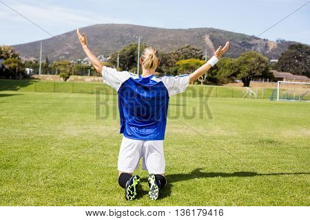 Rear view of female football player posing after a victory on football field