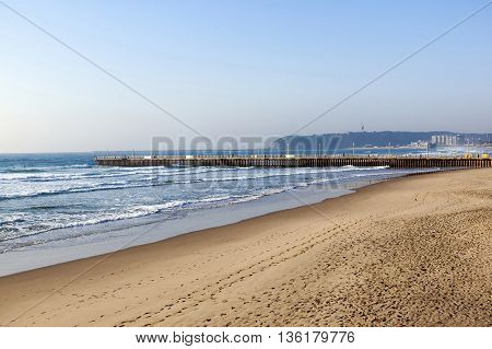 Empty Beach Sea And Concrete Pier Against Blue Sky