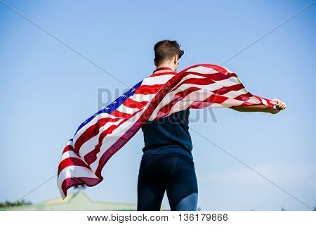 Rear view of athlete holding an american flag