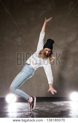 Portrait of talented young dancer posing against of lights and brown urban wall.Studio shot.