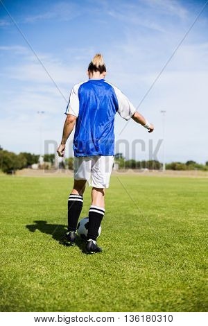 Rear view female football player practicing soccer in a stadium