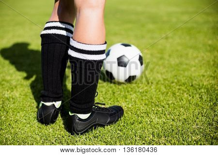 Feet of a female football player and a ball on football field