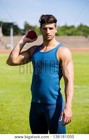 Determined athlete about to throw shot put ball