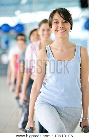 beautiful woman at the gym doing free weight smiling with a group of people behind