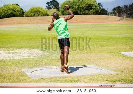 Male athlete preparing to throw shot put ball in stadium