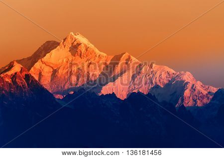 Beautiful first light from sunrise on Mount Kanchenjunga Himalayan mountain range Sikkim India. Orange tint on the mountains at dawn
