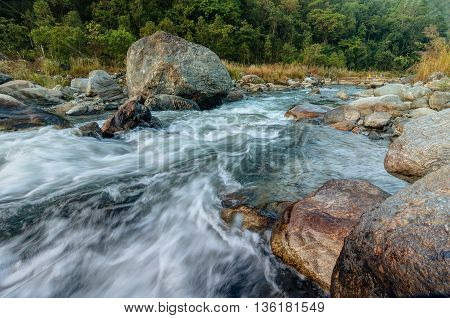 Beautiful Reshi River water flowing on rocks at dawn Sikkim India - a spectacular view tinted image