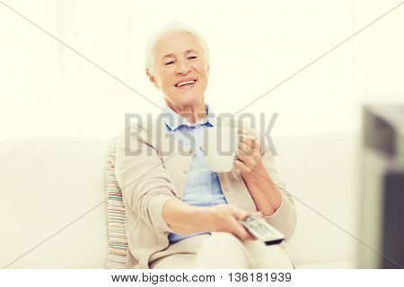 technology, television, age and people concept - happy senior woman watching tv, drinking tea and changing channels by remote control at home