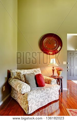 Comfortable armchair with pillows in the corner of the living room. Antique Wall Clock on green wall and polished hardwood floor in the room.